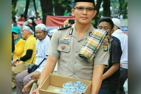 Foto polisi ganteng membagikan minuman kepada peserta aksi Bela Islam Jilid III di Jakarta, Jumat (2/12/2016) beredar viral di media sosial. Masyarakat simpati melihat polisi tersebut. (tobasatu.com/facebook).