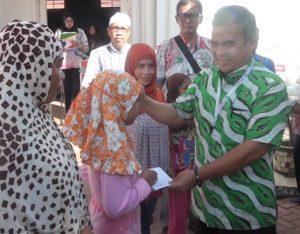 GM Pelindo I cabang Belawan, Sahat Prawira Tambunan sedang memberikan bantuan santunan kepada anak yatim di Belawan (foto : tobasatu.com/ lee)